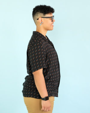 Model wearing a new york toy collective binder under a button up shirt in profile showing off a flat chest