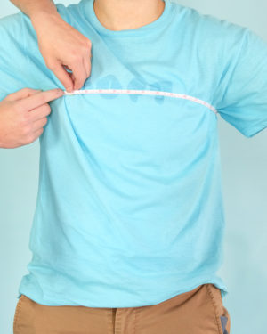 a model in a t-shirt with a tape measure wrapped underneath the models armpits