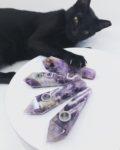 Amethyst pipes on a white background. A Black cat reaches for the pipes with her claws extended